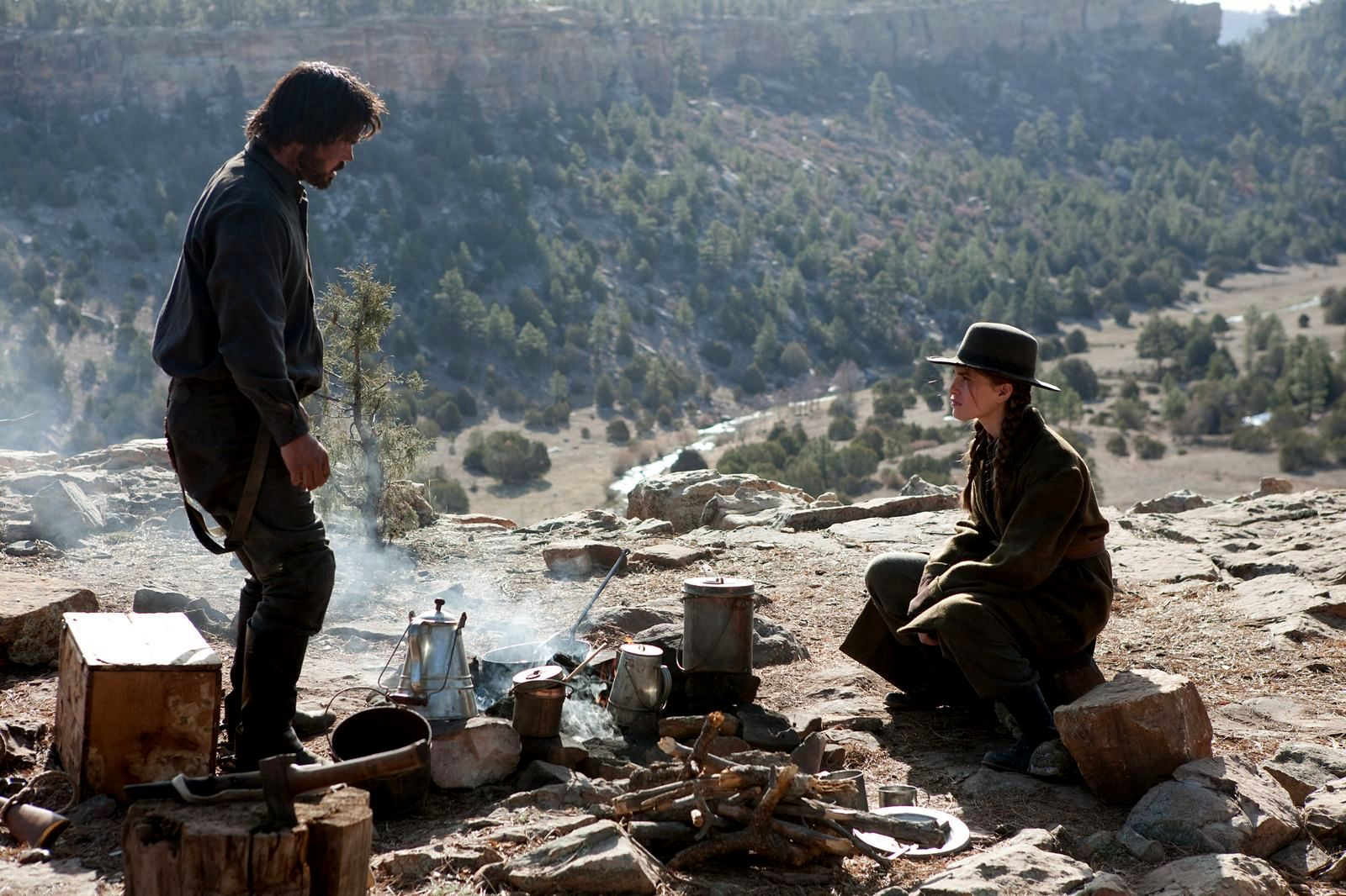 Rooster and Mattie warm up with a cup of coffee, potentially lending the film its title: True Grit. (photo credit: Paramount Pictures)
